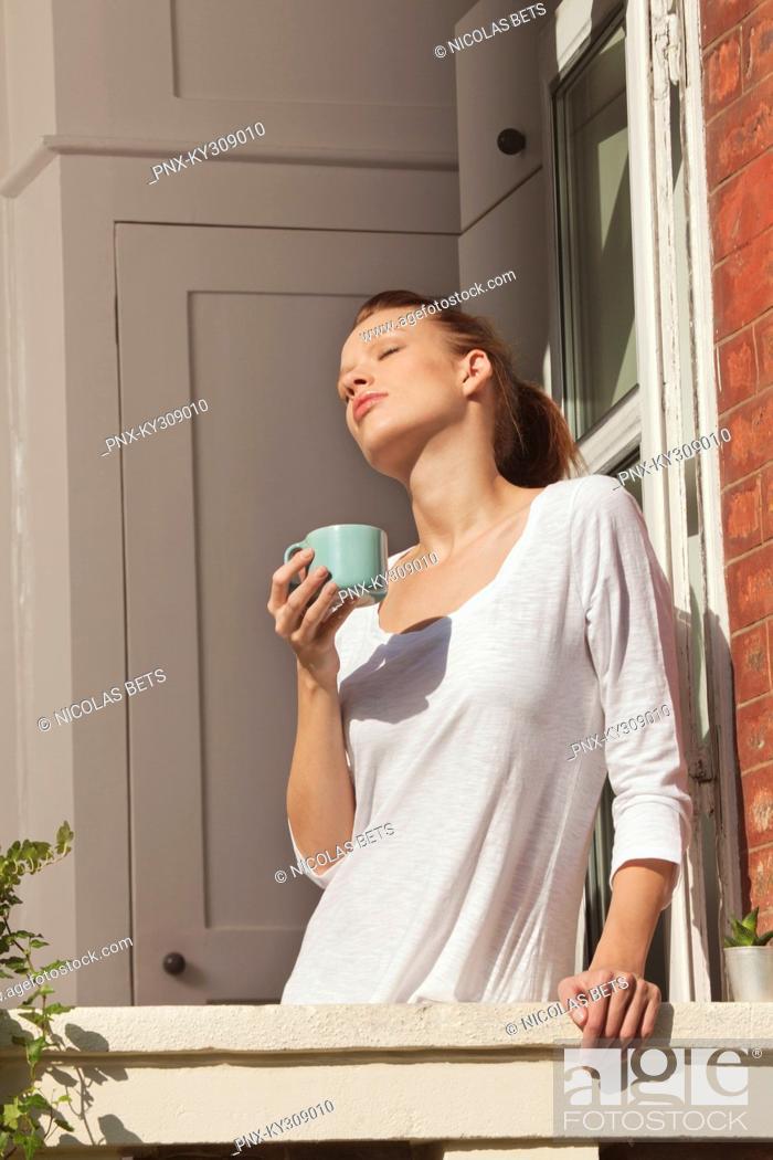 Stock Photo: Young woman enjoying sun at window.