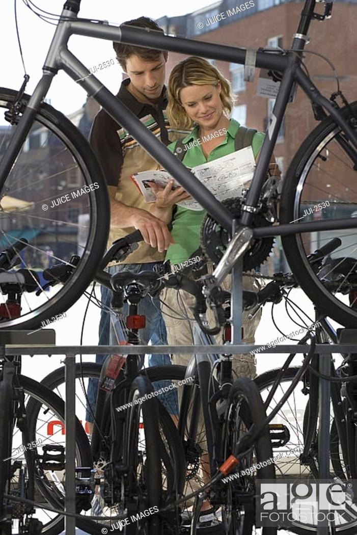 Stock Photo: Young couple shopping for new bike in bicycle shop, looking at brochure, view through bike frame.