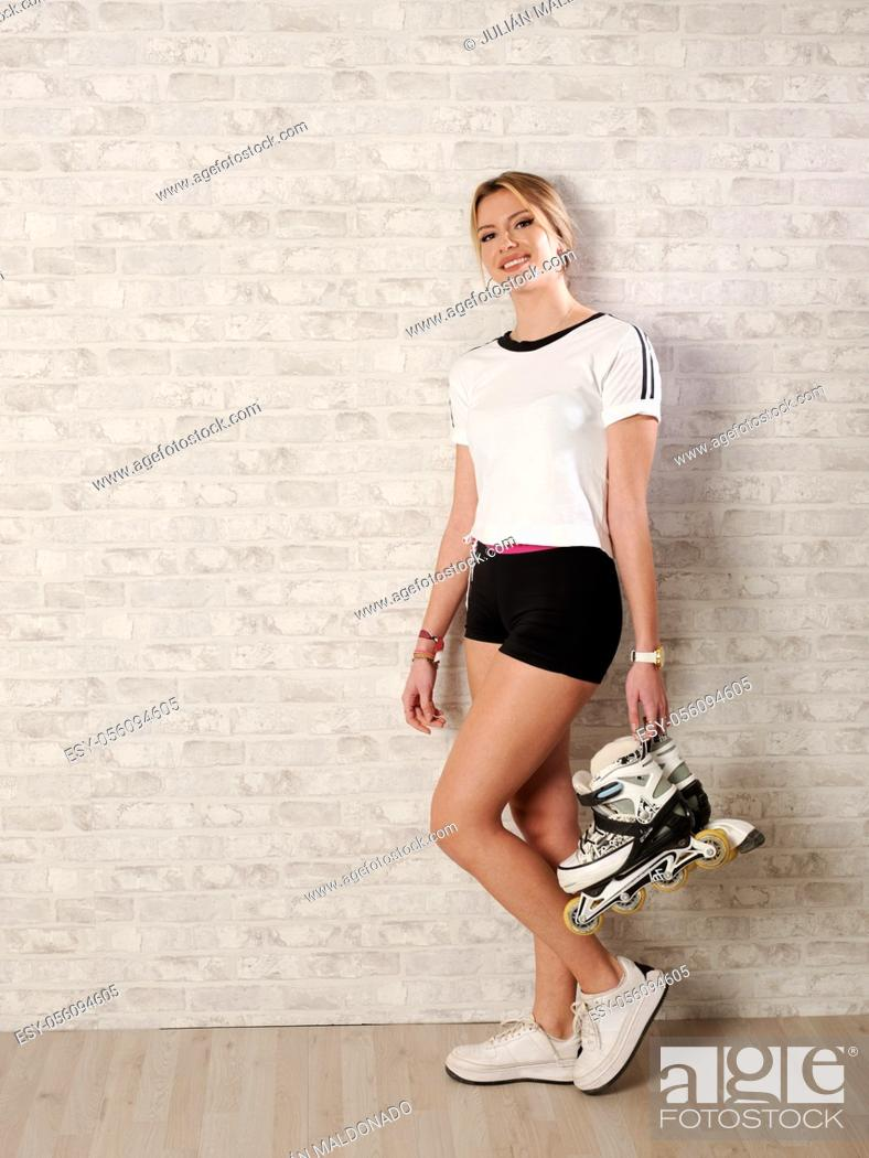 Stock Photo: Beautiful young woman with cheerful fitness and with her skates.