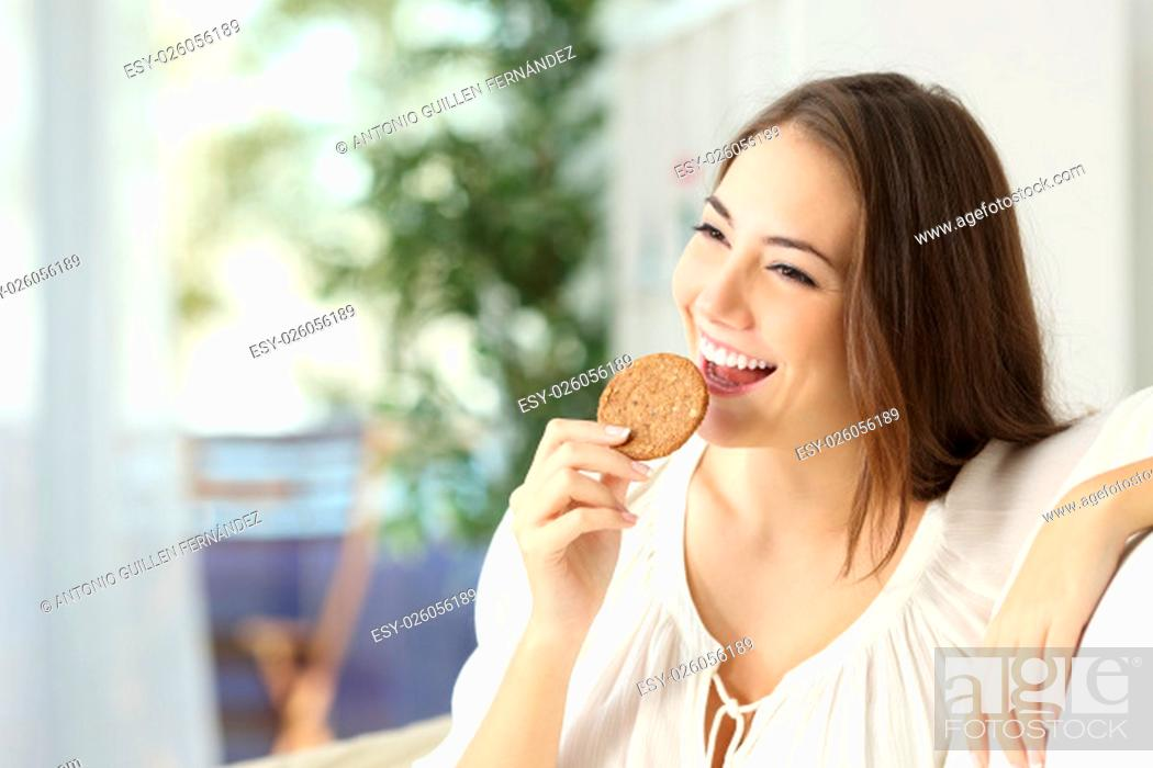 Stock Photo: Happy girl eating a dietetic cookie sitting on a couch at home.