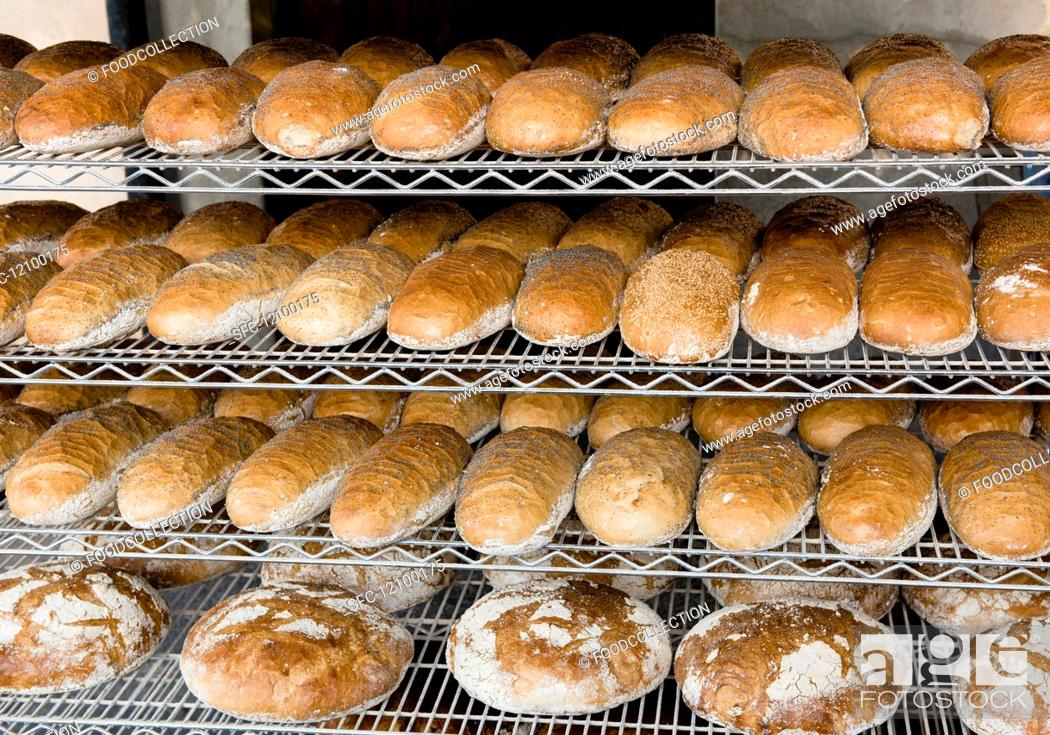 Imagen: Loaves of white bread sprinkled with poppy seeds on shelves in a bakery.