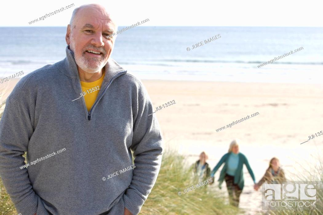 Stock Photo: Senior man standing on beach smiling, portrait, family in background.