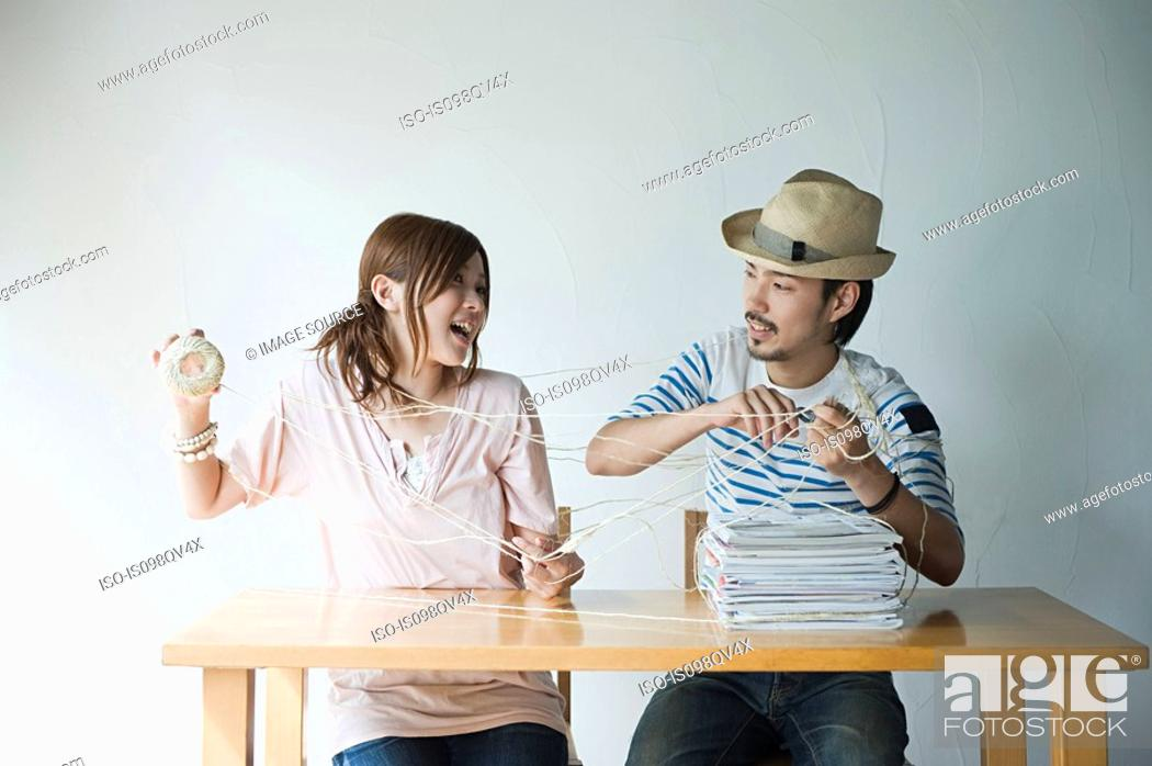 Stock Photo: Young couple with string and magazines.