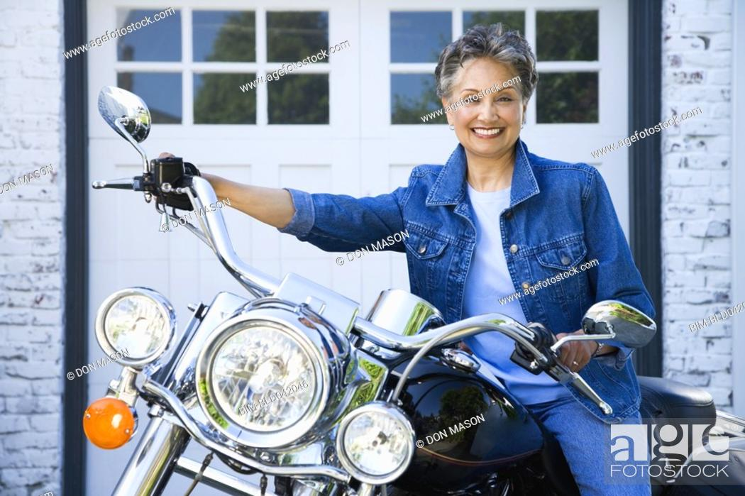 Stock Photo: Senior African American woman sitting on motorcycle.