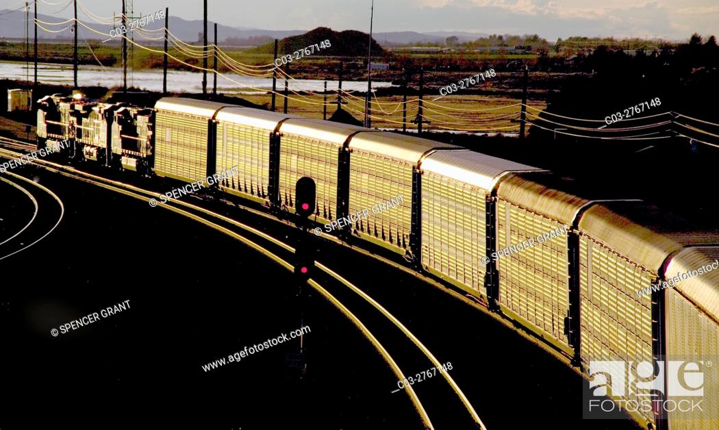 Stock Photo: Afternoon sun shines on a freight train carrying livestock on a curve in Barstow, CA. Note red signal in center.