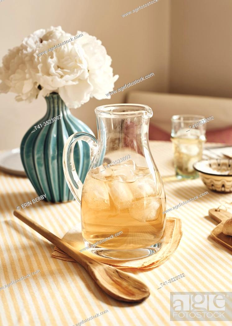 Stock Photo: A pretty table setting in a kitchen, dressed up for brunch or a party, with a pitcher of iced tea.
