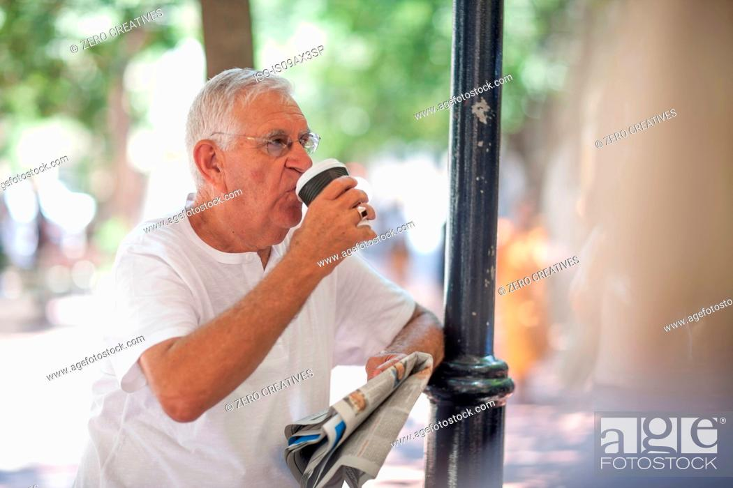 Stock Photo: Senior man drinking takeaway coffee in city.