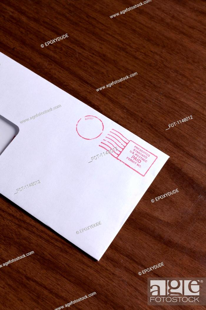 Stock Photo: A window envelope with a red ink postage stamp.