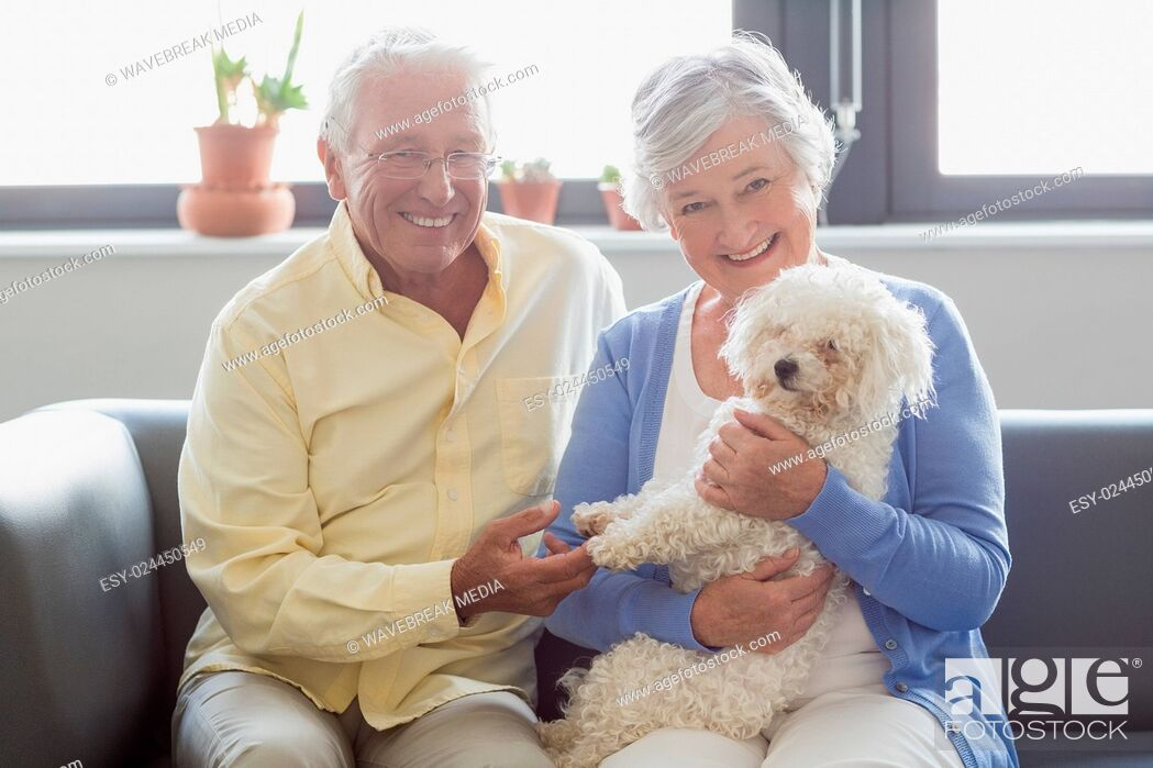Stock Photo: Senior couple holding a dog.