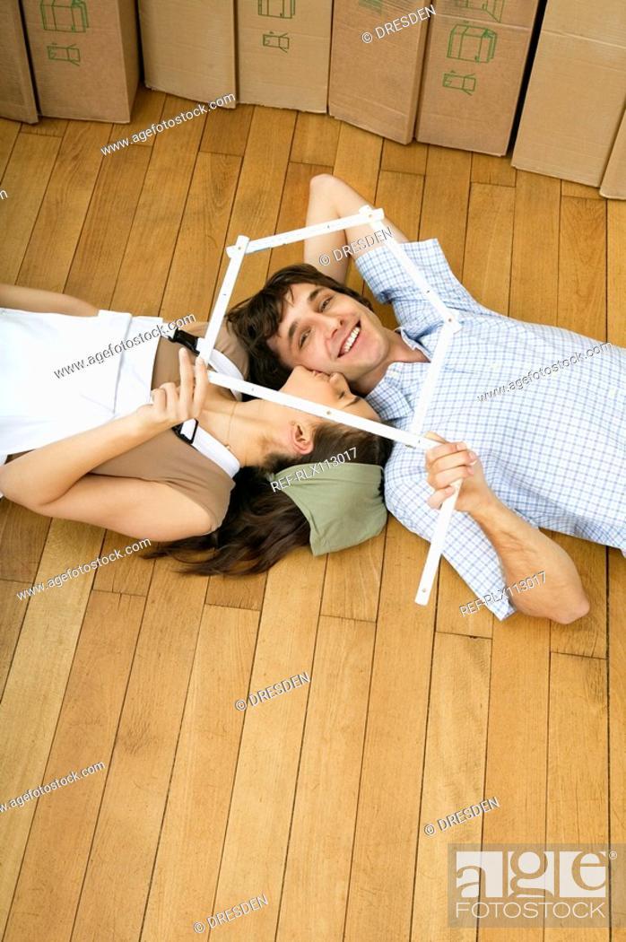 Stock Photo: Young couple lying on wooden floor.