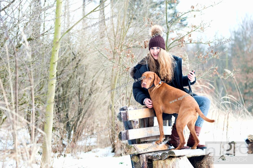 Stock Photo: Cheerful young woman sitting on bench with dog against bare trees in forest during winter.