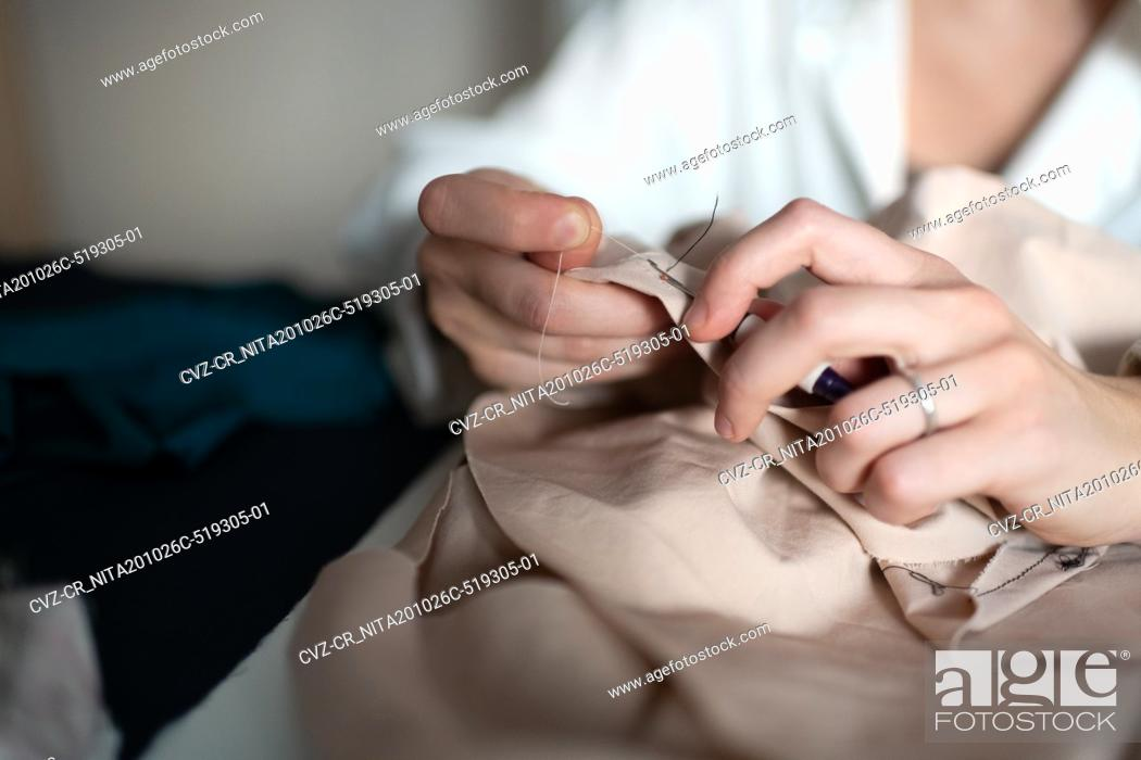 Stock Photo: Cropped dressmaker sewing with needle.
