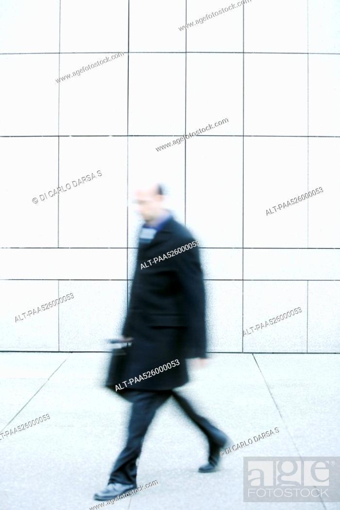 Stock Photo: Businessman walking on sidewalk.