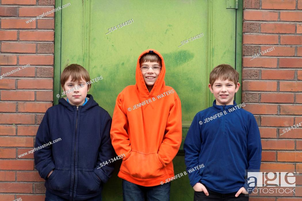 Stock Photo: Three boys outdoors, standing against a building.