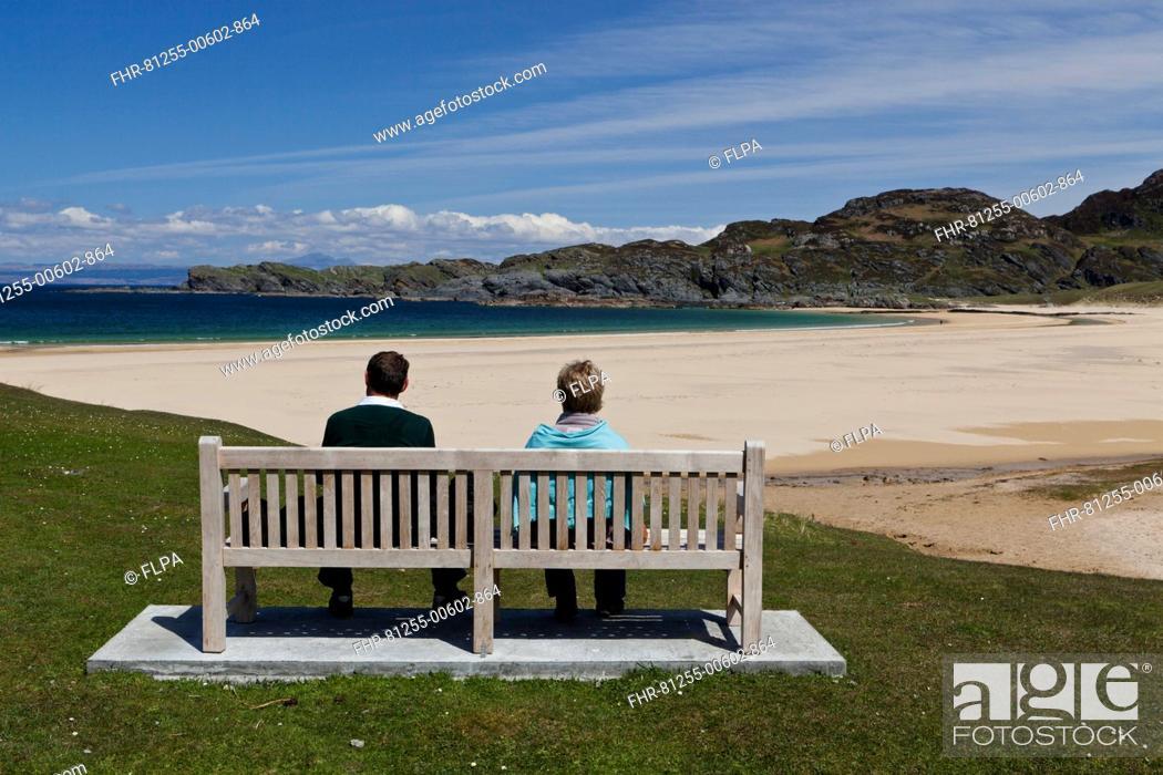 Stock Photo: Couple sitting on bench overlooking coastline with sandy beach, Kiloran Bay, Isle of Colonsay, Inner Hebrides, Scotland.