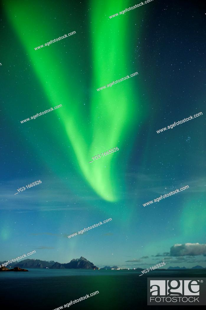 Stock Photo: Northern Lights fill sky over sea and mountains, Stamsund, Vestvagoy, Lofoten islands, Norway.