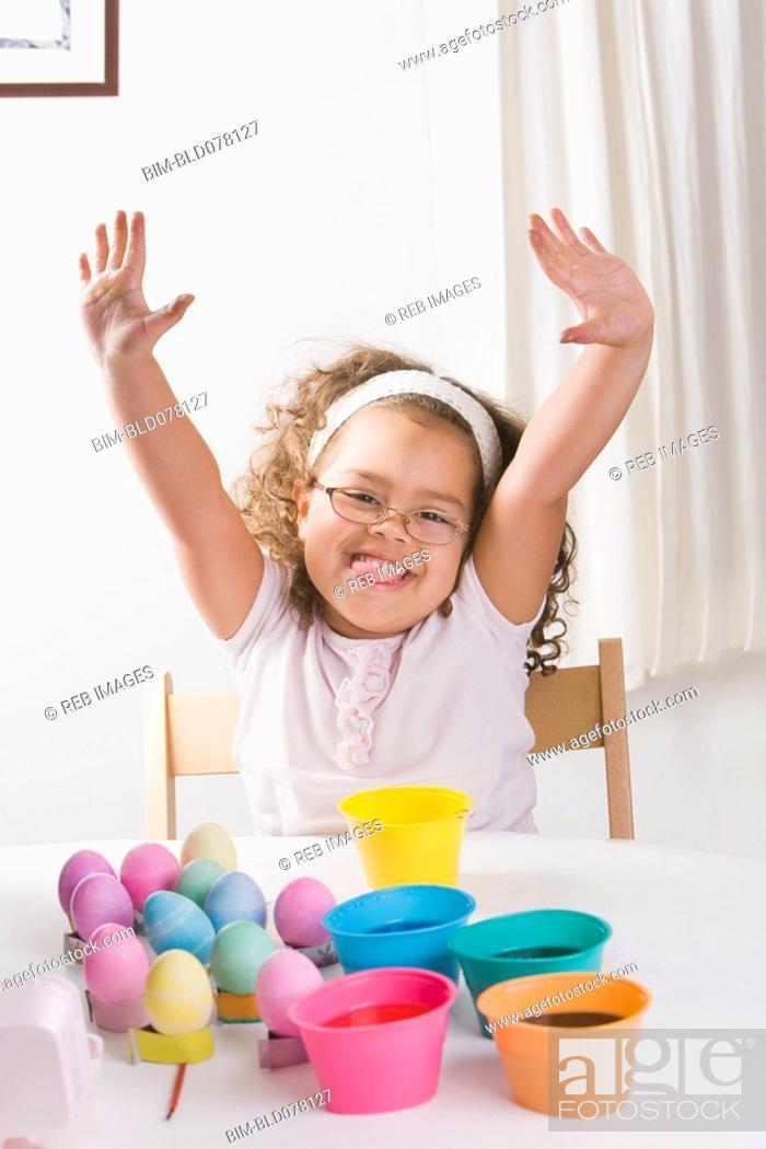 Stock Photo: Hispanic girl decorating Easter eggs.