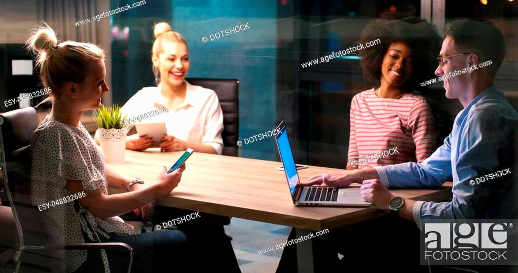 Stock Photo: Multiethnic startup business team on meeting in modern night office interior brainstorming, working on laptop.