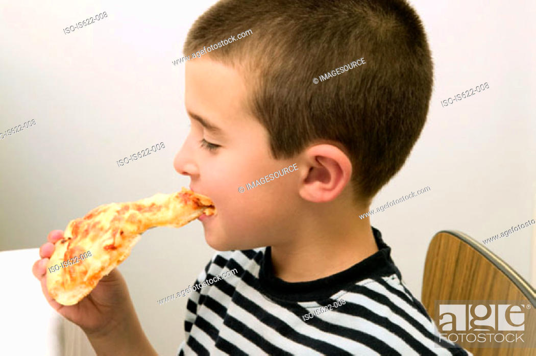 Stock Photo: Boy eating a slice of pizza.