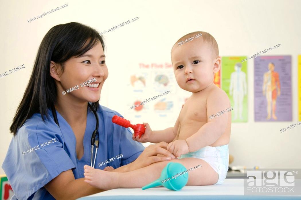 Stock Photo: A nurse and examining a baby.
