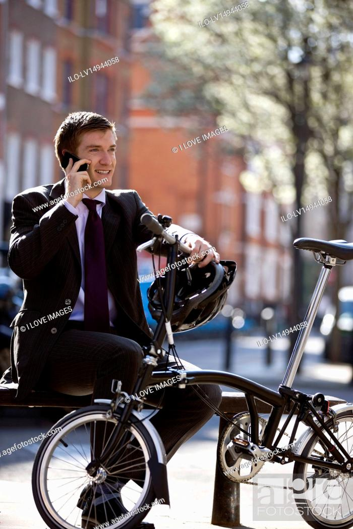 Stock Photo: A businessman sitting on a bench, talking on his mobile phone.