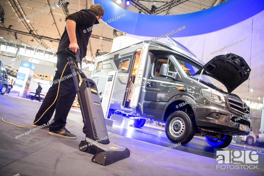 A Man Cleans The Fair Stand Of Caravan Manufacturer Hymer One