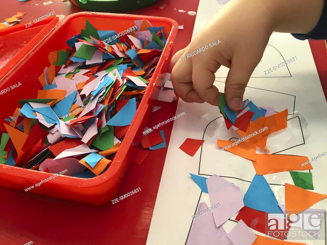 Stock Photo: Child's Hands with Brush, Gluing Coloured Shapes onto Pieces of Paper. . . .