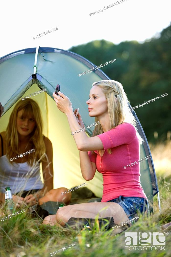 Stock Photo: Two young women camping, one applying make-up.