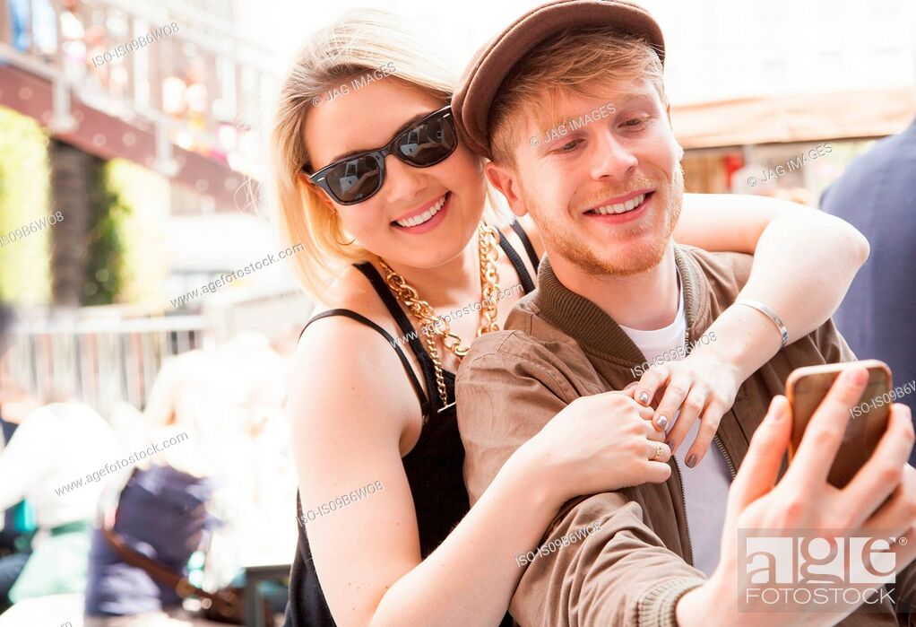 Stock Photo: Young couple, outdoors, taking selfie, using smartphone.