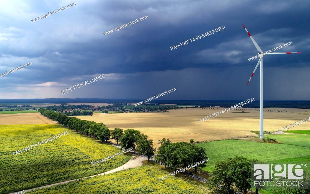 Stock Photo: 13 July 2019, Brandenburg, Petersdorf: Thunderstorm clouds are moving over the landscape with a field of sunflowers in the Oder-Spree district (aerial.