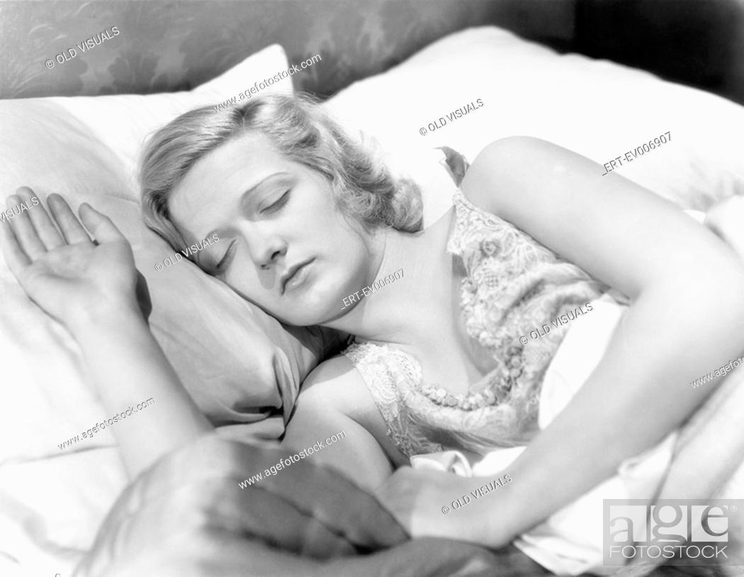 Stock Photo: Young woman lying in her bed sleeping All persons depicted are not longer living and no estate exists Supplier warranties that there will be no model release.