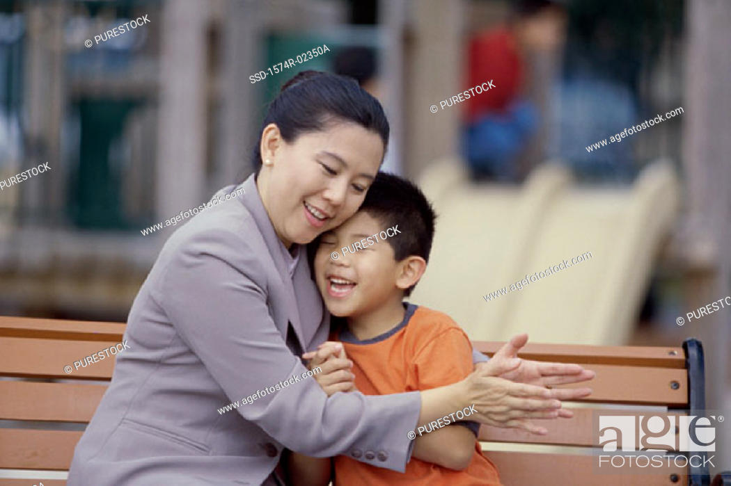 Stock Photo: Mother hugging her son sitting on a park bench.