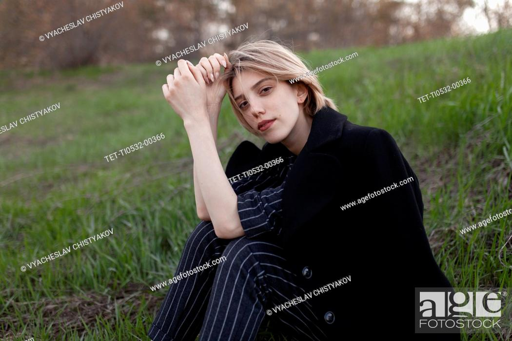 Stock Photo: Russia, Omsk, Portrait of young woman sitting in grass.