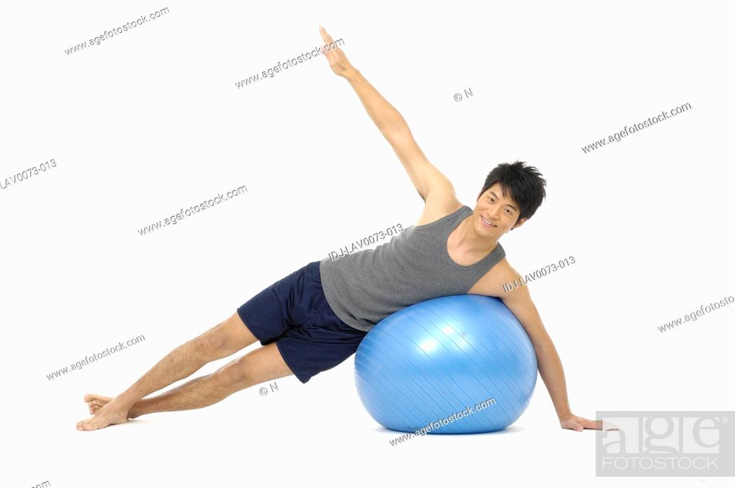 Stock Photo: Young man doing yoga with a fitness ball.