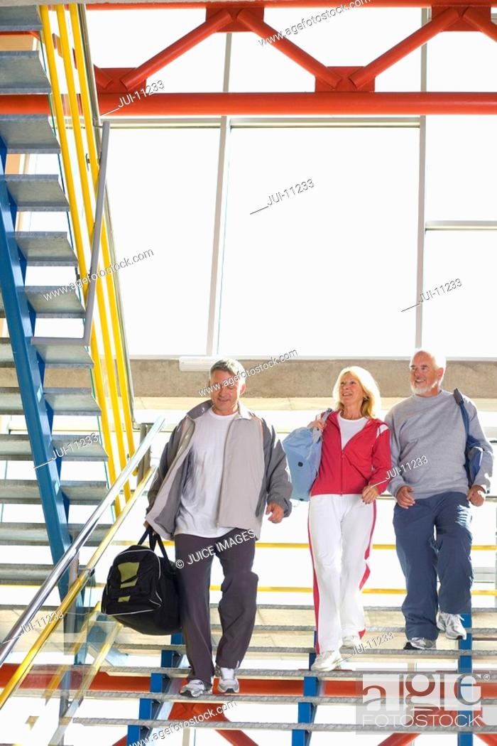 Stock Photo: Two senior men and woman with gym bags walking down steps, low angle view.