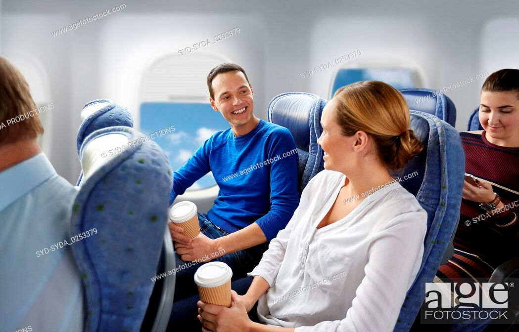 Stock Photo: happy passengers with coffee talking in plane.