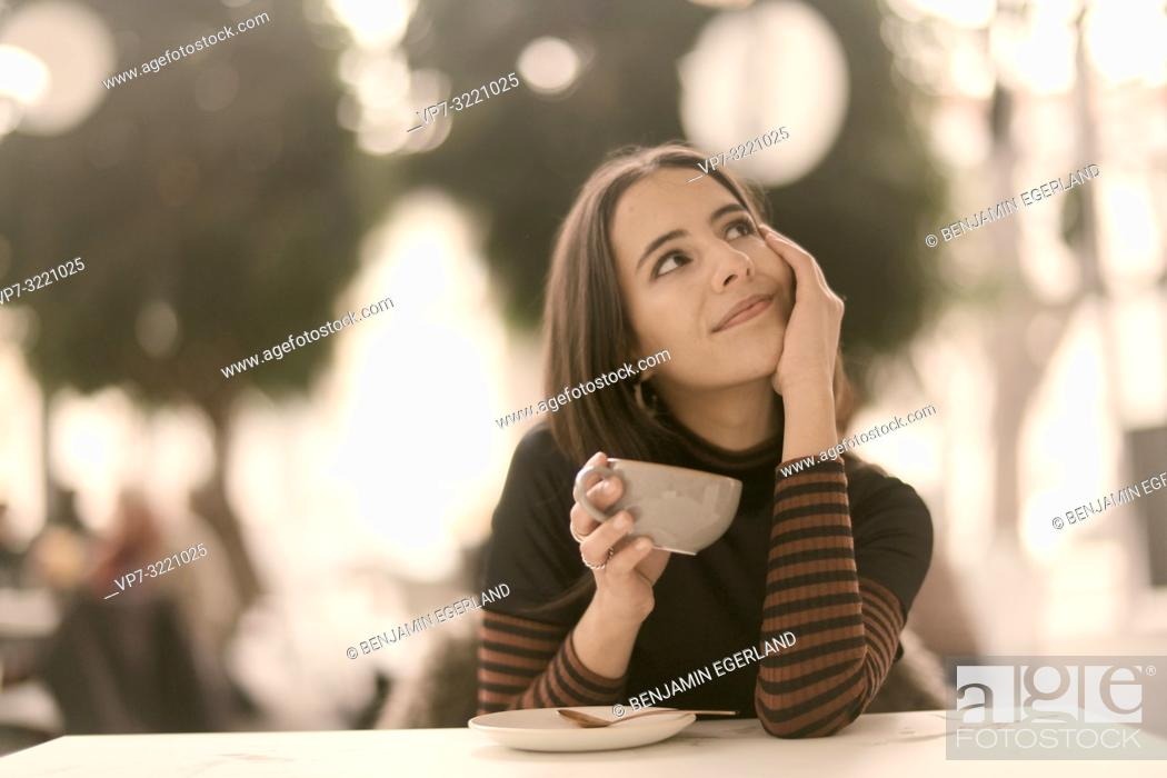 Imagen: portrait of pleased woman holding coffee cup while enjoying break at table in café, looking to side, in Munich, Germany.