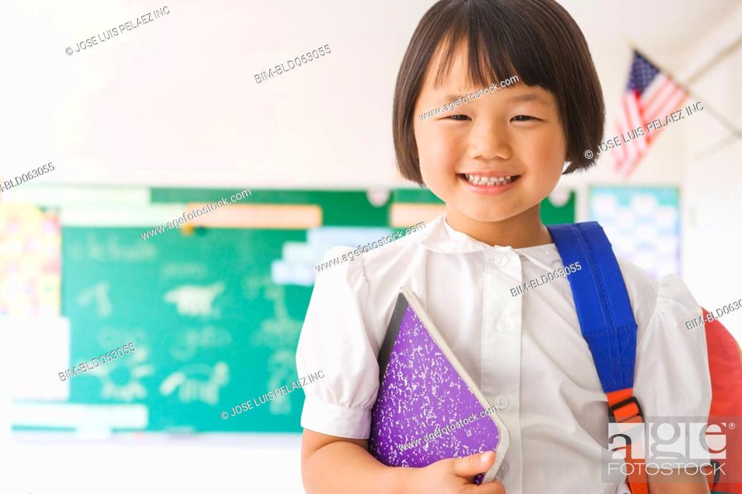 Stock Photo: Asian girl holding backpack and notebook in classroom.