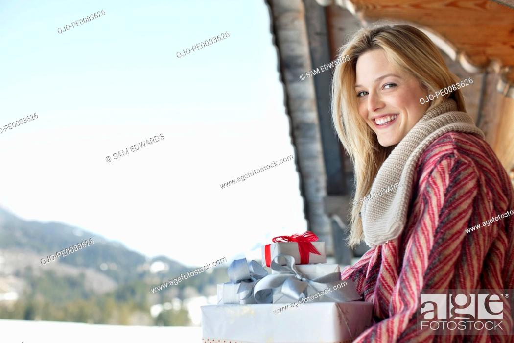 Stock Photo: Portrait of smiling woman with Christmas gifts.