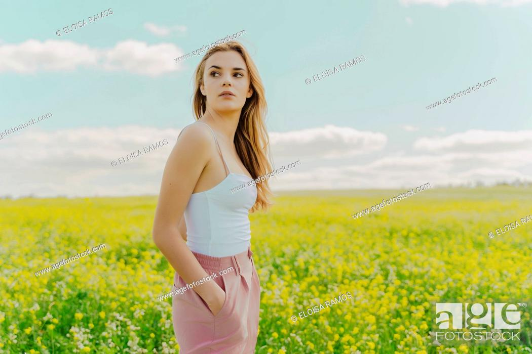 Stock Photo: Young woman standing in a flower meadow in spring.