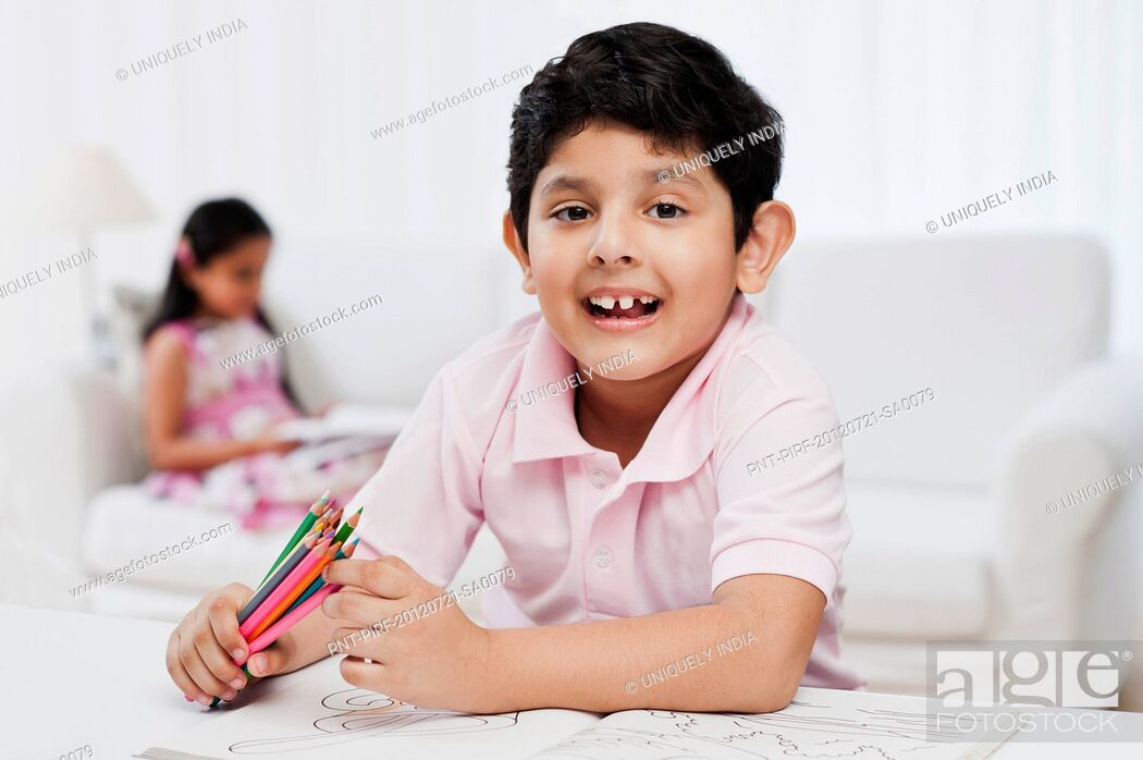 Stock Photo: Boy making drawings with his sister in the background.