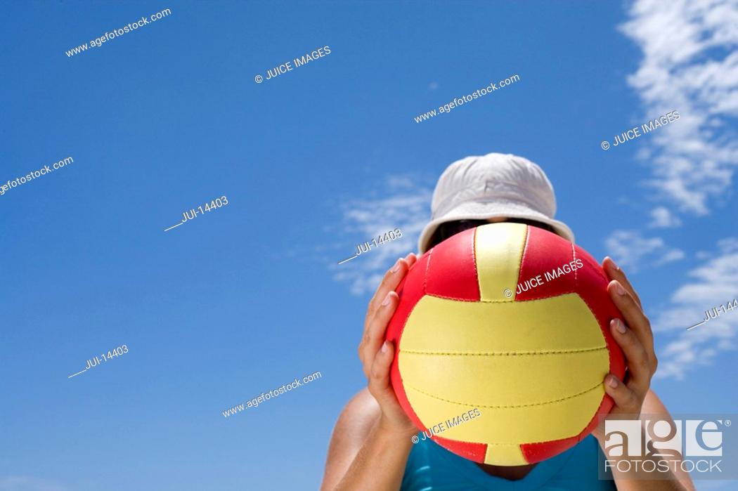 Stock Photo: Man obscuring face with ball outdoors, low angle view.