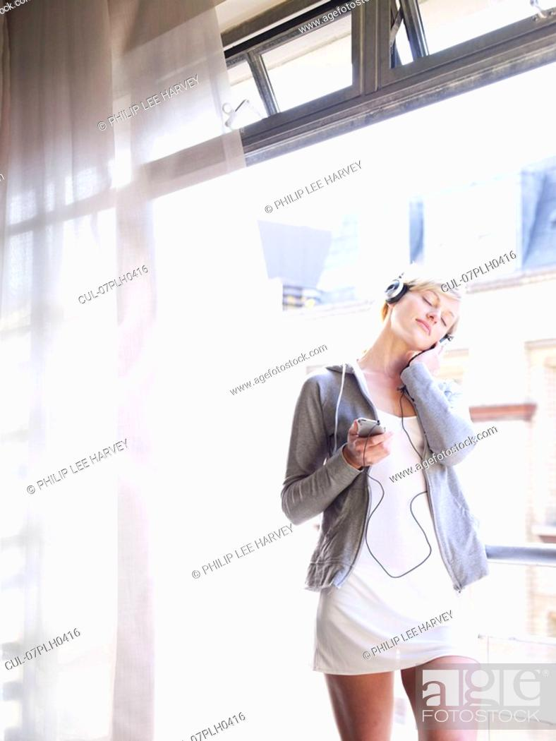 Stock Photo: Woman listening to music at window.