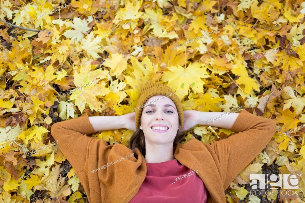 Stock Photo: Brunette Woman in Park in Autumnn smiling at camera, view from above.