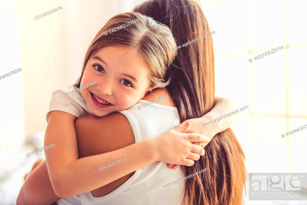 Stock Photo: Beautiful young woman and her charming little daughter are hugging and smiling.