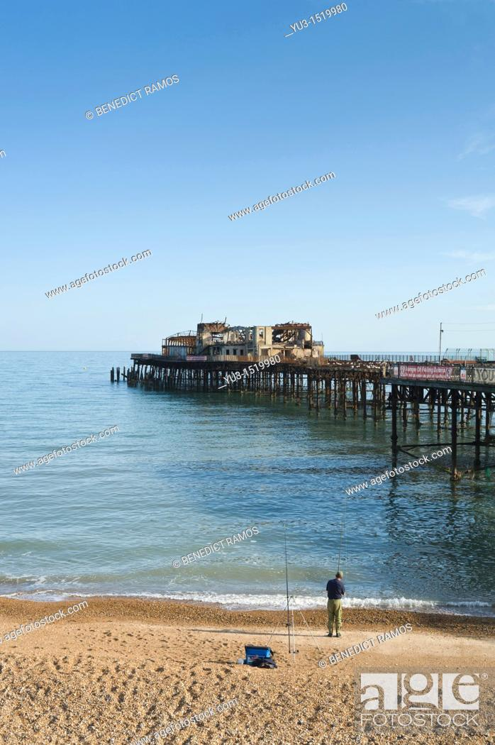 Stock Photo: Man fishing on the beach by the pier, Hastings, East Sussex, England, UK.