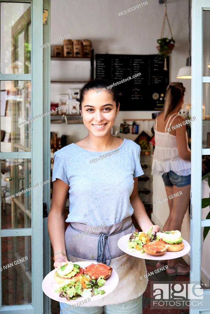 Stock Photo: Portrait of smiling waitress serving breakfast.