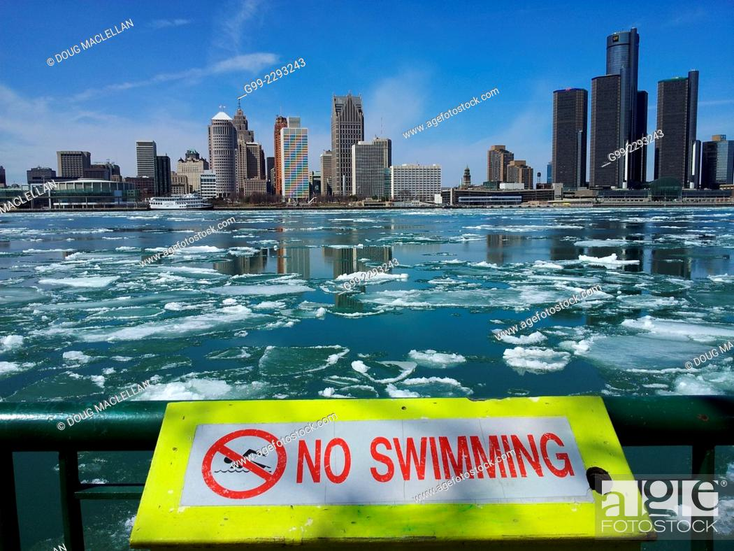 Stock Photo: Spring ice breaking, Detroit skyline (no swimming sign, ship passing.), Windsor, Ontario, Canada.