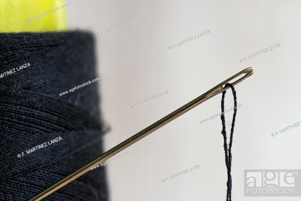 Imagen: Spool of black thread with needle.