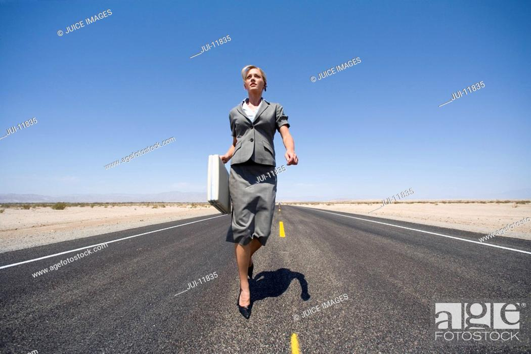 Stock Photo: Businesswoman walking in middle of road in desert with briefcase, low angle view.